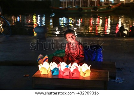 Hoi An, Vietnam - May 18, 2016: A young boy selling handmade lanterns to tourists in the streets of Hoi An.