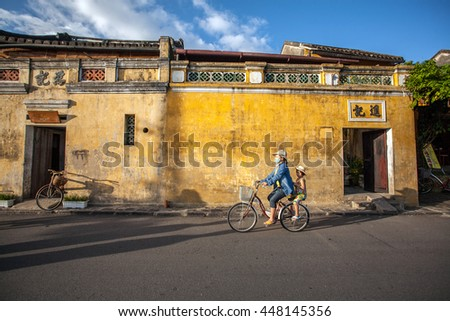 HOI AN, VIETNAM - OCTOBER 21: Unidentified Vietnamese cycling at riverfront of Hoi An old town. it was declared a World Heritage Site by UNESCO on Oct 21, 2014 in Hoi An, Vietnam
