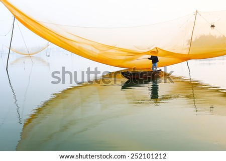 HOIAN, VIETNAM-JAN 23: Unidentified fisher man check his nets in early morning on river at January 23, 2015 in Hoian, Vietnam. Hoian is recognized as a World Heritage Site by UNESCO. - stock photo