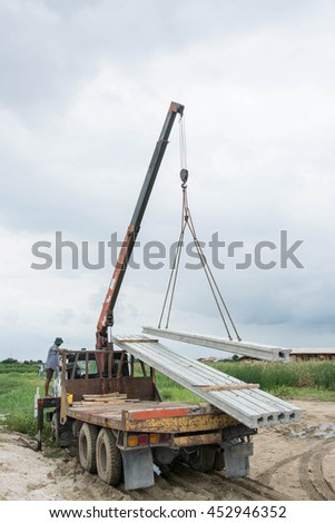 hoisting  concrete pole piles with crane using metal slings