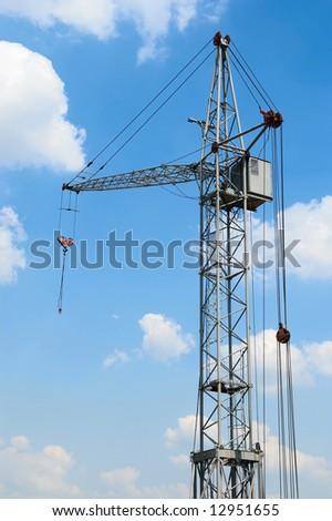 hoisting crane against blue sky - stock photo
