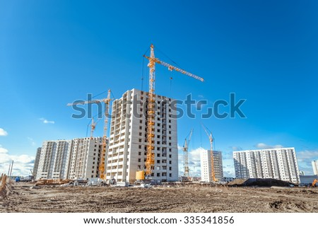 Hoisting cranes and building activity - stock photo