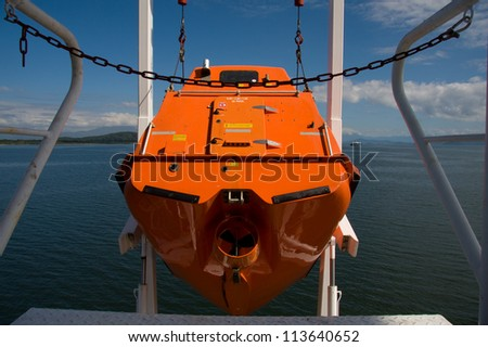 Hoisting ship's free fall life boat after training drill.