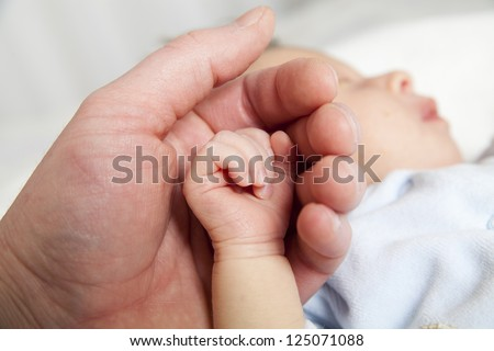 hold a hand of the newborn child