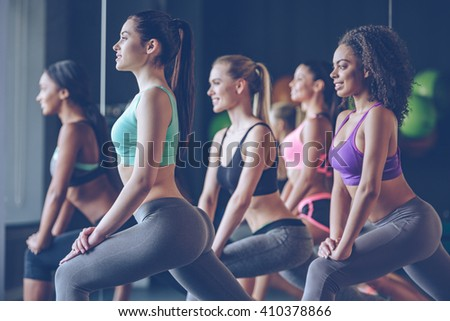 Hold it girls! Side view of beautiful young women with perfect bodies in sportswear exercising with smile at gym - stock photo