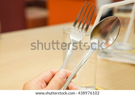 hold spoon and fork with human left hand in restaurant background - stock photo