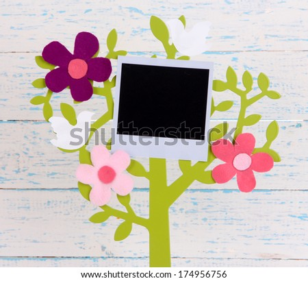 Holder in form of tree with instant photo card on wooden background - stock photo