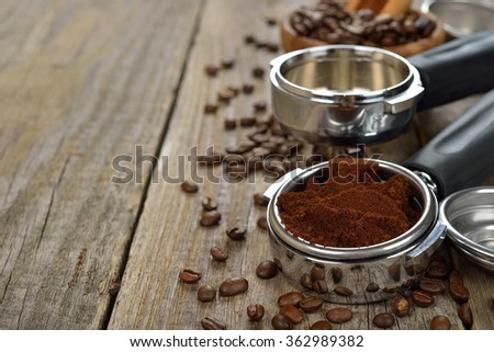 Holder with ground coffee on a wooden background - stock photo