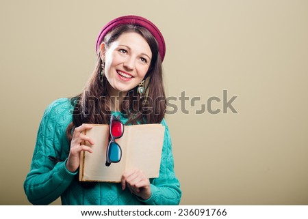 holding a book & 3d glasses hipster or hippie pretty girl having fun wearing knitting sweater happy smiling and looking at camera over copy space background  - stock photo