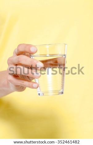 Holding a glass of fresh water - stock photo