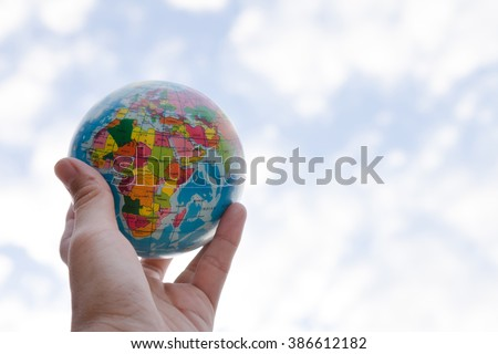 holding a globe in his hand on blue sky background, environment and business concept - stock photo