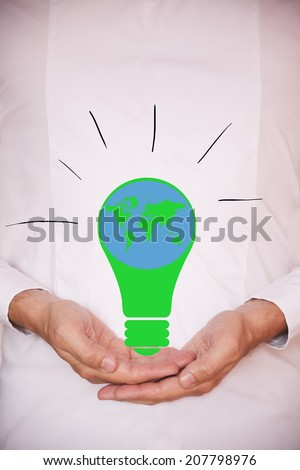 Holding a green light bulb with world map on it - stock photo