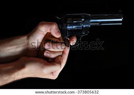 Holding a handgun on a dark background - stock photo