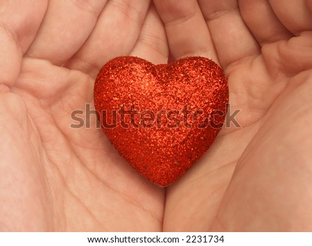 holding a heart shaped ornament in hand