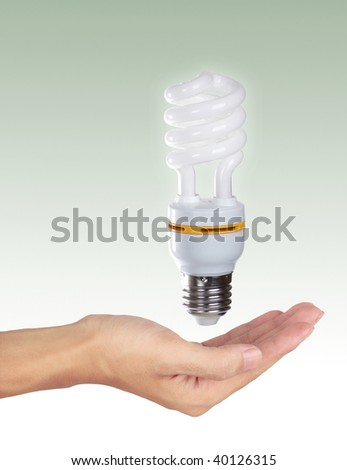 Holding a light bulb. Isolated on a Green background.