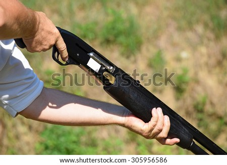 Holding a shotgun in hands - stock photo