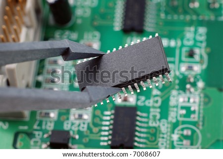holding an integrated circuit chip with printed circuit board as back ground