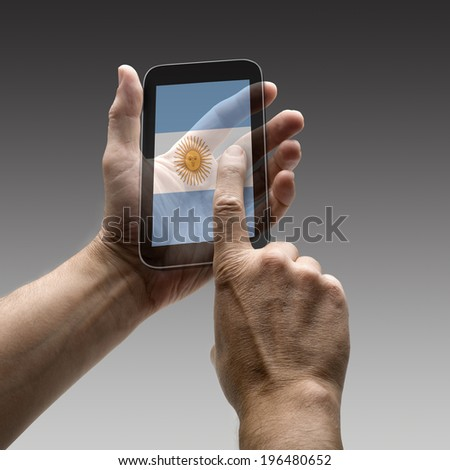 Holding Argentina flag screen smart phone. There is a route for hand and finger.  - stock photo