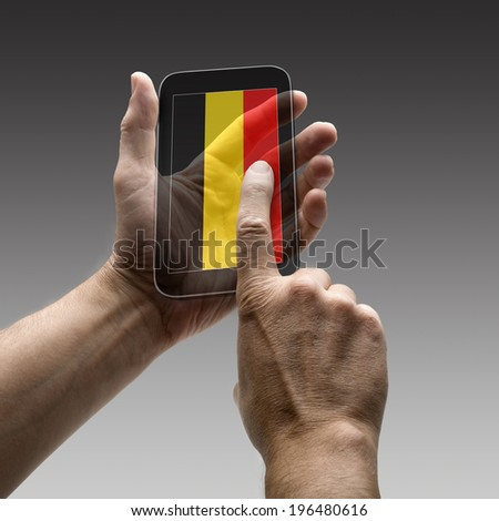 Holding Belgium flag screen smart phone. There is a route for hand and finger.  - stock photo