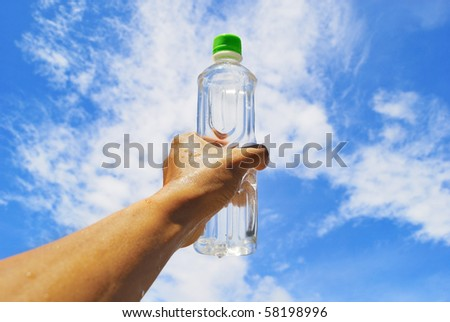 Holding bottle and sky - stock photo
