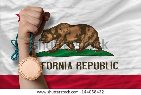 Holding bronze medal for sport and flag of us state of california - stock photo