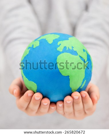 holding clay earth globe, saving project - stock photo
