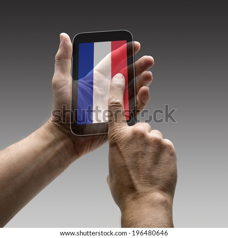 Holding French flag screen smart phone. There is a route for hand and finger.  - stock photo
