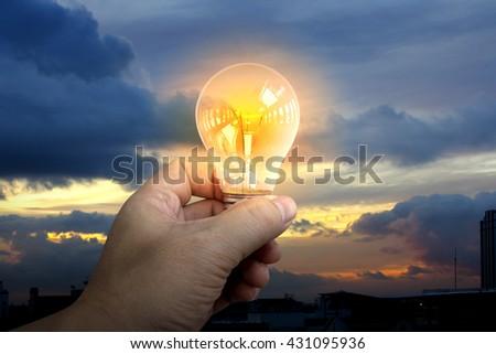 holding glowing light bulb over dark sky background - stock photo
