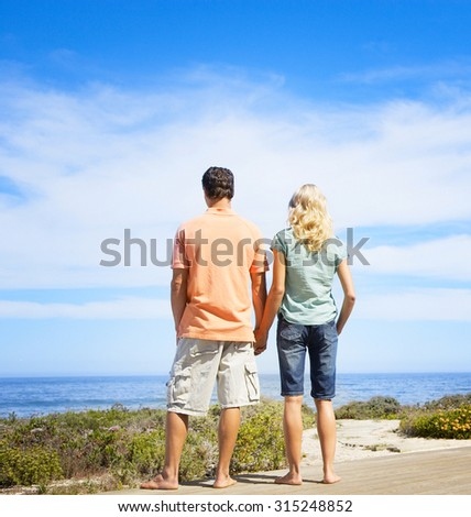 Holding hands couple on beach - stock photo