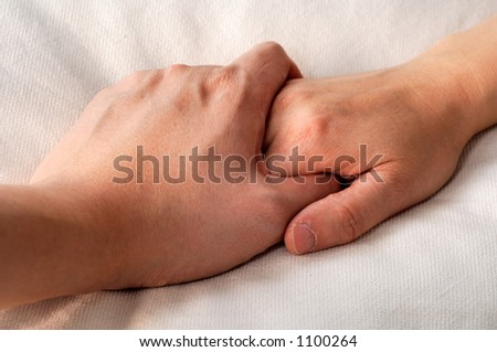 holding hands in bed - stock photo
