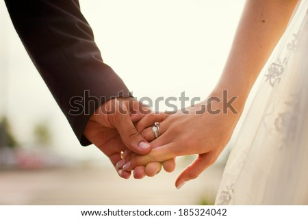 holding hands on the sunset - stock photo