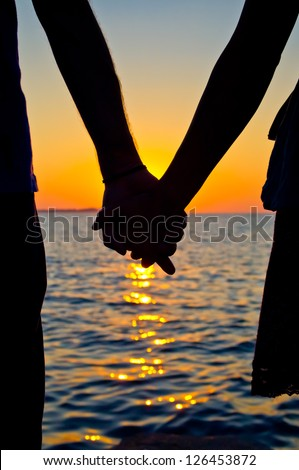 Holding Hands with love in the sunset on the sea - stock photo