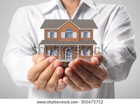 holding house representing home ownership and the Real Estate  - stock photo