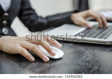 Holding laptop mouse - stock photo