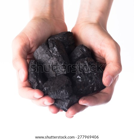 Holding lumps of charcoal in hands - stock photo
