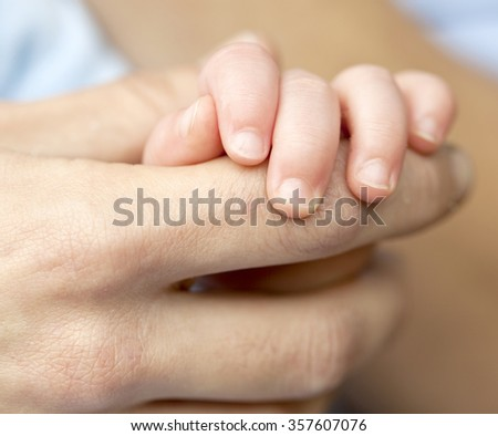 Holding my Father's Finger. A young baby boy holds onto his father's finger. There is a contrast between the young baby hand and skin and the hard worked skin of his father.