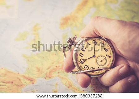 Holding old pocket watch in hand with map of Europe behind - stock photo