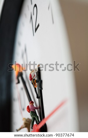 Holding On To Time, macro of miniature model mountaineers scaling the hands of a clock, shallow DOF. - stock photo