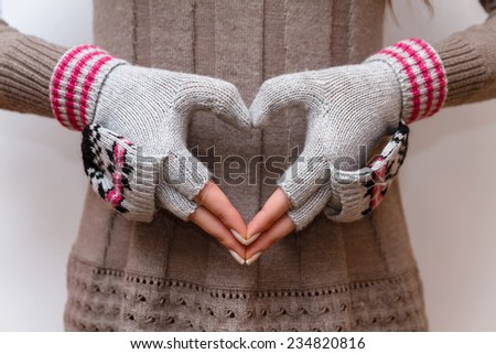Holding Out a Heart Sign with hands in mittens on sweater background - stock photo