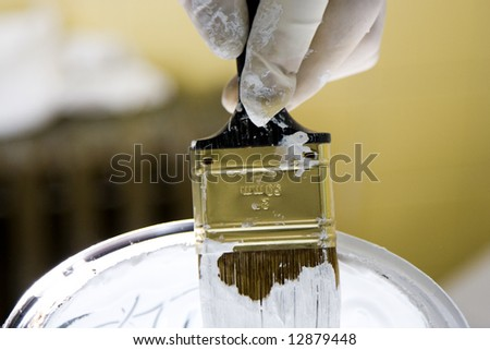 Holding Paintbrush in White Bucket - stock photo