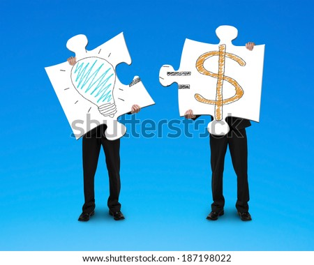 Holding 2 puzzles with bulb and money symbol drawing blue background - stock photo