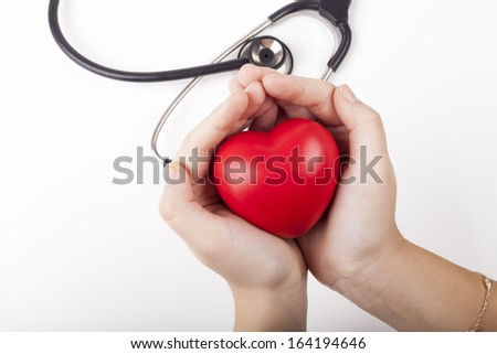 Holding red heart in two hands with black stethoscope in the background isolated on white - stock photo