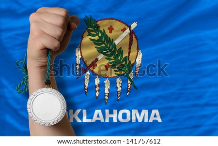 Holding silver medal for sport and flag of us state of oklahoma - stock photo