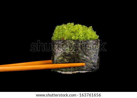 holding sushi with chopsticks isolated on black - stock photo