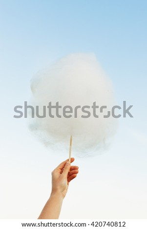 Holding Sweet Cotton Candy on Stick on Blue Sky background
