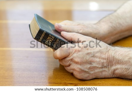 holding the bible over table - stock photo