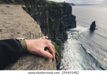holding tight at the edge of a cliff, POV - stock photo