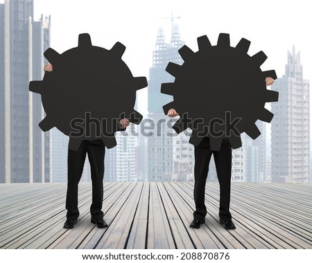 Holding two gears to connect on wooden floor with city view background - stock photo
