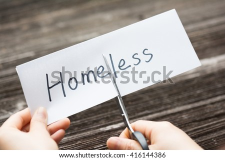 holds card with text homeless on old wood plate - stock photo