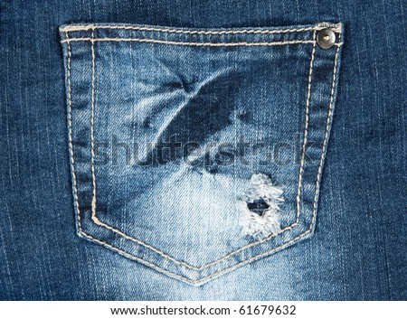 Hole in a pocket of worn out old blue jeans. - stock photo